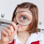 Picture of girl with magnifying glass over one eye to make it look much bigger