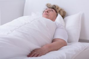 lady lying completely flat in bed
